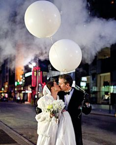After the ceremony, they created their own Big Apple moment by leading their guests -- all carrying white balloons -- down Fifth Avenue to their reception at the Harvard Club (Eric attended the university).  Here, the couple sneak a peck while leading their nearest and dearest in a Midtown balloon parade.