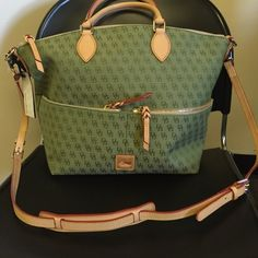 NWT Dooney &Bourke handbag Light green with a tan trim! Never used! Has two handles but the option to use as a crossbody bag! Front of the purse have two zippers to store lots of stuff Dooney & Bourke Bags