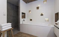 Designéři připojili ke koupelně část vedlejší komory, získali tak prostor pro velký sprchový kout.