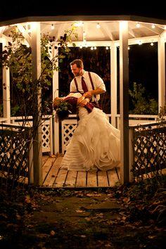 groom dips bride in a gazebo with christmas lights wedding