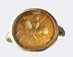 An amber coloured cornelian seal decorated with a rider holding a spear and mounted on a rearing bull. The seal is mounted in a later gold ring.  Seal: Roman, c. 2nd or 3rd Century AD; ring: mid 20th Century AD