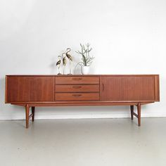 Very nice mid-century sideboard with a drop down cabinet, 3 drawers and the right cabinet has a door that slides 'invisible' into the back of the sideboard.