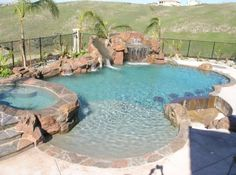 This custom swimming pool designed and built by Lifetime Pools features a waterfall, grotto, slide and sunken bar.