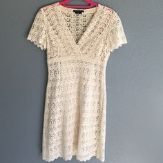 """Flash SaleBCBG MaxAzria Crochet Dress So pretty and feminine! BCBG Max Azria cream colored crochet cross front dress with short sleeves. Features side zipper and empire waist - dress has poly knit under slip in cream. length from shoulder seam to hem is 37.5"""", bust from under arm pit seam to seam is 15.5"""". waist flat across is 13.75"""", hips 16.75"""". Excellent condition - no stains or flaws. 87% cotton 13% rayon for dress, liner is 85% poly 15% spandex. **price firm unless bundled**. 6D2054…"""