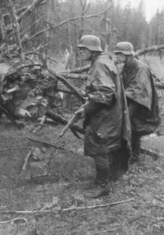 Ww2 • Southern Russia Spring 1942 • Two German grenadiers, wearing rain capes, approach enemy positions with their rifles ready.
