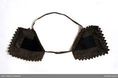 Örnasvansar ca 11 x 11 cm, 2 st lappar av svart kläde kantade med släta svarta sidenband och med uddar av svart sicksackband, sekundärt hopsatta med ett brunt bomullsband. Sattes ett vid varje öra under kluten. Vemmenhögs härad, ca 1840-70. Nordiska Museet, nr. NM.0014857A