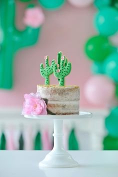 Naked birthday party cake. Pink and green cactus cookie cake toppers. Fresh pink decorative flower. White cake plate. Cactus Party styling by Happy Wish Company. Photography by Tammy Hughes Photography. Stationery by Minted artist, Baumbirdy.