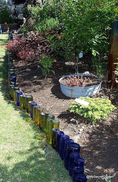 Using wine bottles as a border in the garden, this is what I was planning to do... but I need to drink more wine, and I plan to burry them a little bit deeper.... This would look so pretty with lights behind the glass!!