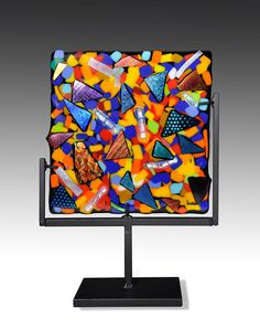 Swizzle Panel by Helen Rudy . A dazzling rainbow of opaque and dichroic glass is fused in a kiln to become a striking work of art to brighten home or office. Includes its own stand to easily set on a window ledge or mantle. Each is unique; exact colors and patterns will vary. Signed by the artist.