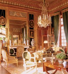 The living room of Paris-based designer Jacques Garcia's home in the Château du Champ de Bataille glows with luxurious paneling and gold-framed portraiture.