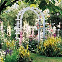 Paint can add a style boost to a simple arbor without overwhelming a vibrant garden setting. This white arbor stands in contrast to a riotous display of colorful flowers./