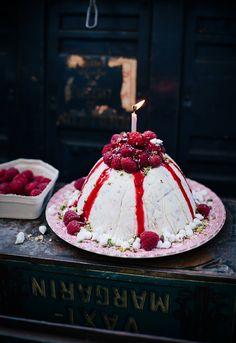 Vanilla ice cream cake with raspberries, pistachios, meringue drops and raspberry sauce