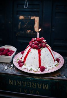 Vanilla ice cream cake with raspberries, pistachios, meringue drops and raspberry sauce