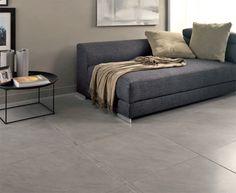 #salon avec carrelage gris, mur gris-beige - allié à un canapé gris foncé et à une table basse en métal noir