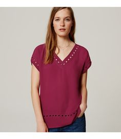This easy tee dresses up with eyelet studded woven front - and soft knit back. V-neck. Short dolman sleeves. Side slits.