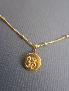 Om Necklace, Tiny Om pendant necklace, Gold Om charm on 14K Goldfill Satellite Chain. Visit  Lotus411 more buddhist jewelry. by Muse411 on Etsy https://www.etsy.com/listing/124216042/om-necklace-tiny-om-pendant-necklace