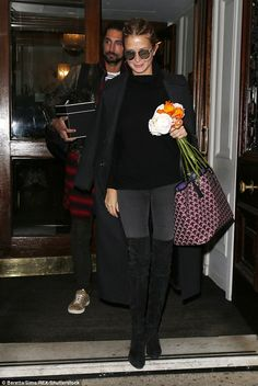 Good night? Smiling Millie Mackintosh clutched flowers as she left Browns hotel in London with Hugo Taylor on Friday... after branding him the perfect 'Insta-boyfriend'