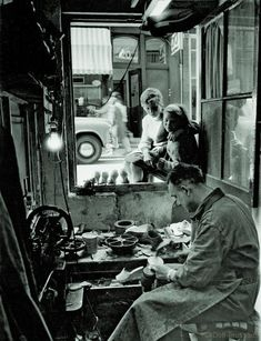 1960's. Shoemaker repairs shoes in his shop at the Nieuwe Leliestraat in the…
