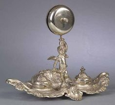 An Antique Silvered Metal Hotel Desk Stand in the Rococo Taste, 19th c., the reticulated scroll and foliate base supporting two covered inkwells and a standing putto holding a bell