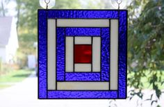 I made this beautiful Log Cabin Quilt stained glass panel using a textured red stained glass for the center block, textured cobalt blue stained glass and a streaky tan/amber stained glass for the outlining blocks. It measures 10 x 10 and is framed in zinc. It can hang from two suction cups which I will provide or I will attach a chain for hanging. Please let me know what you would prefer at check-out.  This would be a beautiful addition to any window in your home!  All items in my shop a...