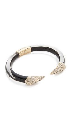 A hinged, lucite Alexis Bittar cuff bracelet with crystal-encrusted spike ends.