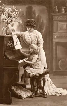 Little girl learning piano from her mother