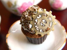 These cute little steam-punk cupcakes come with a tiny gear nestled in the frosting. They'd make great earrings!