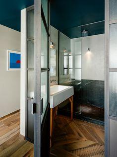 A custom steel door opens onto the master bathroom. Davey Lighting Mast lights brighten the concrete and marble shower.