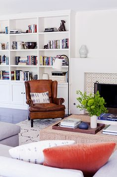 love this room with built in shelves and leather chair reading nook