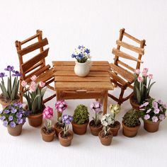 Miniature garden props - potted flowers, wooden table and rickety chairs
