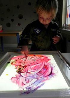 Utilisez la table lumineuse pour renforcer l'impact visuel des couleurs lors d'un atelier peinture.