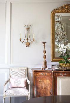 French dining room boasts a gilt French mirror placed over an antique curved buffet cabinet placed next to a French armchair upholstered in Mary McDonald Vanderbilt Velvet Dove Fabric accented with a pink pillow illuminated by a brass 2 light sconce, Oslo Sconce.