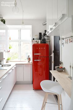 Te white walls and units make the red Smeg fridge the feature of the kitchen, despite its awkward placement.