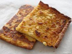 ΥΛΙΚΑ : 1,5 φλυτζάνι αλεύρι 1 φλυτζάνι νερό 2-3 αυγά 1,5 φλυτζάνι τυριά τριμμένα (κυρίως φέτα) 6 κουτ. σούπας ελαιόλαδο (2 για το ζυμάρι και 4 για το ταψί) αλάτι, πιπέρι Σ' όποιον αρέσει τρίβει μέσα λίγο δυόσμο ή ρίγανη ΕΚΤΕΛΕΣΗ Σ' ένα μεγάλο