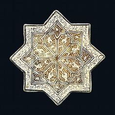 A KASHAN COBALT AND LUSTRE POTTERY STAR TILE CENTRAL IRAN, DATED 8 JUMADA I AH 738/2 DECEMBER 1337 AD Of eight-pointed form, decorated with geometric design outlined in cobalt-blue on a ground of vines and large flowerheads, inscription including date in naskh around the border, dark brown outline, repaired breaks