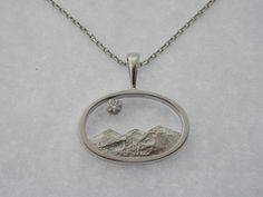 Oregon's Three Sisters oval picture frame pendant in 14kt white gold with 0.04ct round brilliant diamond.