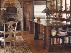 Rustic meets whimsical in this grand, inviting kitchen. The fireplace is made of stone that was found on the property. The painting next to the built-in refrigerator is an unexpected touch amidst the traditional details.