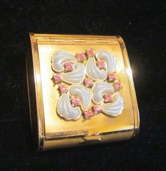 This is a pretty pink rhinestone and powder blue decorative design powder and mirror vanity compact from the 1950's. The piece features a shiny and brushed gold tone exterior, with a gold plated inter