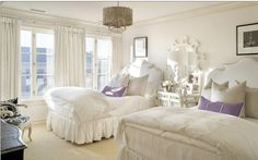 White guest bedroom two beds with purple accent pillow and silver ceiling fixture