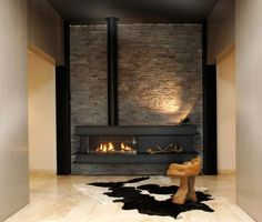 Love the lines with this contemporary wood FIREPLACE- the exposed pipe is interesting. Great stone work