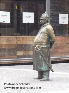 """""""Uncle Charlie"""" 2008 - Already a tourist favorite, it was modeled after the grandfather of the artist, András Illyés, who was indeed a policeman, and used to look like this, though he could only wear this particular helmet on public holidays.  Located in District V, corner of Október 6 utca and Zrínyi utca  Budapest Hungary"""