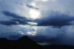 TITLE -minimal mountain storm clouds | the sun breaks through the middle of a patch of dark stormy clouds above a minimalist California mountain landscape