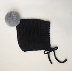 A white pom bonnet with a pom color like mustard, or grey.