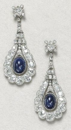 A Pair of Art Deco Diamond and Sapphire Ear Pendants , 1920  Each designed as an old-cut diamond tear drop-shaped plaque, centering upon a cabochon sapphire, mounted in white gold and platinum, length 1 3/4 inches.