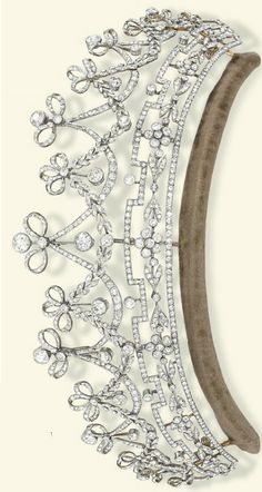 A BELLE EPOQUE DIAMOND TIARA Designed as a series of graduated old-cut diamond garlands each surmounted by a ribbon bow and diamond collet suspending articulated knife-edge bar and circular-cut diamond drops, above a stylised geometric foliate frieze, mounted in platinum and gold, circa 1905, 23.5 cm inner circumference, in original fitted blue leather case. This tiara was formerly the property of Lady Emilie Harmsworth