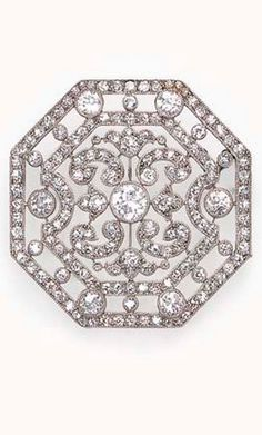 A BELLE EPOQUE DIAMOND BROOCH, BY CARTIER  Designed as a pierced openwork octagonal-shaped single-cut diamond frame, bezel-set with old European-cut diamonds and diamond scrolls, mounted in platinum, (accompanied by a screwdriver and seed pearl neckchain, 34 ins.), circa 1910, with maker's mark, in a Cartier red leather case Signed Cartier, no. 5580 (indistinct)