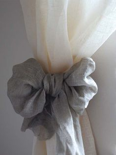 I love this. Buy inexpensive curtains and dress them up with a big bow. You don't have to worry about wasting money on new curtains everytime you change your decor. Just change the bow!