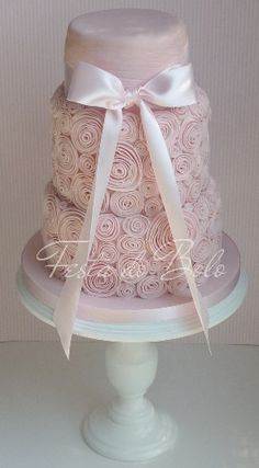pink wedding cake with light pink ribbon and various size of pink swirls