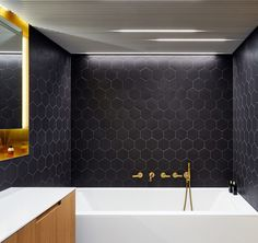 This modern bathroom is done in black, white and brass for an elegant and laconic look