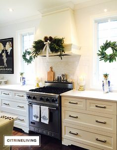Elegant greens used in a swag on the classic range hood are flanked by magnolia wreaths in the windows in the sophisticated kitchen | CHRISTMAS HOME TOUR | CITRINELIVING